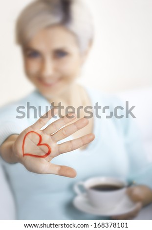 Happy blonde with a cup of coffee shows palm with a painted heart