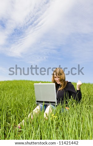 Happy blonde with a laptop in a meadow, arms raised
