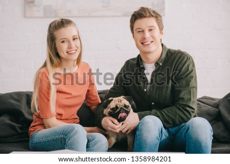 happy blonde woman and handsome cheerful man sitting with cute pug dog on sofa