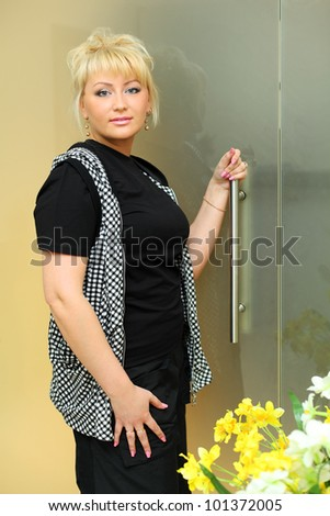 Happy blonde woman dressed in black shirt and checkered vest stands near transparent door and keeps handle