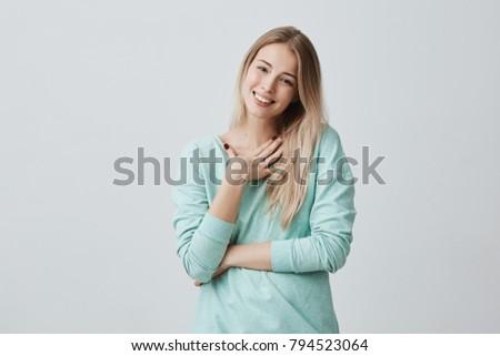 Happy blonde woman glad to recieve present from husband has joyful expression, smiles broadly with teeth. Beautiful pleased female model in light blue sweater expressing positive emotions #794523064