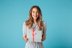 Happy blonde woman in dress holding gift box and looking at the camera while enjoys over blue background