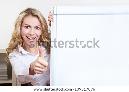 Happy blonde woman in her office with flipchart holding thumbs up