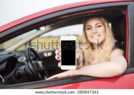 Happy blonde woman showing smartphone out the window of a car. Focus on mobile phone.