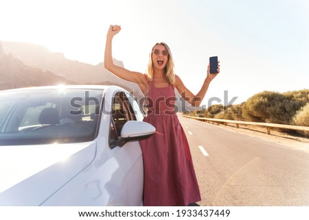 Happy blonde woman with mobile phone in one hand standing near the car, using navigation online to get to her dream destination on holidays. Tourist lifestyle. Real people emotions. Traveler.