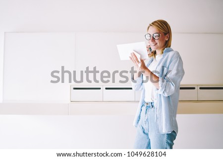 Happy blonde young woman in eyeglasses received letter with good news about winning discounts in webstore and calling to internet consultant to check information on smartphone standing near mailbox