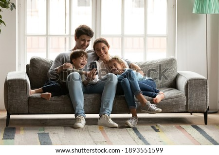 Happy bonding family with two adorable small kids looking at cellphone screen, laughing at funny video or photos in social networks, holding distant video call with grandparents, having fun at home.