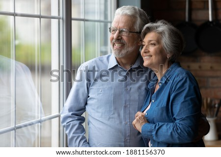 Happy bonding loving middle aged senior retired couple standing near window, looking in distance, recollecting good memories or planning common future, enjoying peaceful moment together at home.