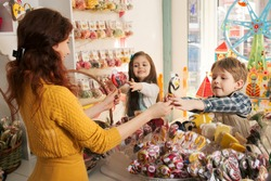 Happy boy and girl buying sweets in the store. Beautiful woman salesman gives candies to children
