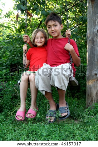 happy boy and girl sitting on swing