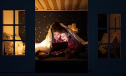 Happy boy and girl sitting under blanket and watching cartoon on tablet on comfortable illuminated bed at night at home