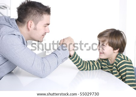 Happy boy and his father arm wrestling