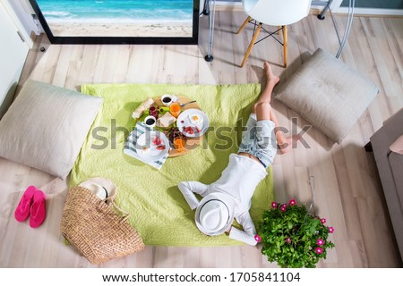 Happy boy are imitating picnic lying on grass on an open air on green grass at home near TV screen. Have fun with family. Coronavirus situation in tourism industry. Quarantine. Isolation from covid19