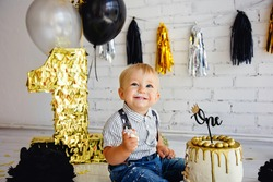 Happy boy blonde 1 year old on his birthday tries sweets. The photo zone with the first cake is decorated in black and gold. Crashcake