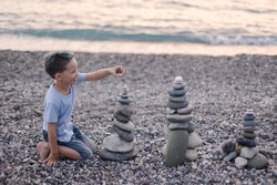 Happy boy builds a cairn of stones on the sea coast. Beach games with children. Leisure in the evening on vacation with kids. Balance development building fantasy. Childhood. Fun joy. Ocean trawel