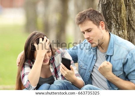 Happy boy celebrating that his sad friend is breaking up by chat sitting on the grass in a park