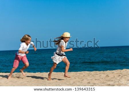Happy boy chasing girlfriend on sunny beach.
