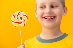 Happy boy child holding tasty lollipop candy on a yellow background