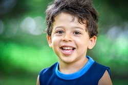 Happy boy child is smiling enjoying adopted life. Portrait of young boy in nature, park or outdoors. Concept of happy family or successful adoption or parenting.