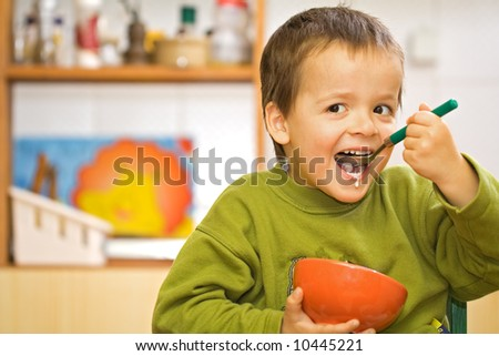 Happy boy eating cereals with milk in the kitchen