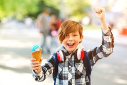 Happy boy eating colorful ice cream in waffles cone. Boy on a summer walk in a park. Kid with delicious gelato.
