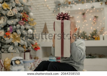 Happy boy found a gift box under the Christmas tree