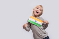 Happy boy holding flag of India and makes funny faces. Learning hindi.