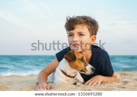 Happy boy hugging his dog breed Jack Russell terrier at the seashore against a blue sky close up at sunset. Best friends rest and have fun on vacation, play in the sand against the sea summer #1310695280