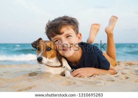 Happy boy hugging his dog breed Jack Russell terrier at the seashore against a blue sky close up at sunset. Best friends rest and have fun on vacation, play in the sand against the sea summer #1310695283