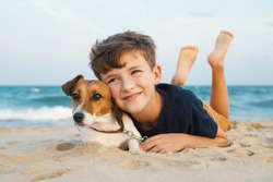 Happy boy hugging his dog breed Jack Russell terrier at the seashore against blue sky close up at sunset. Best friends rest and have fun on vacation, play in the sand against the sea summer