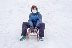 Happy boy in a protective mask sits on a sled. Sledding outdoors in the mountains the winter. Isolation quarantine of coronavirus, covid-19. Winter rest and activities in the snow. Christmas Holidays