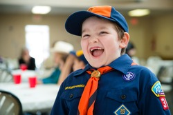 Happy boy in Cub Scout uniform at annual awards banquet in candid image