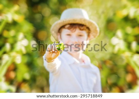 Happy boy in hat holds lucky four leaf clover. Focus on clover #295718849