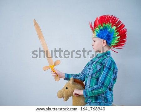 happy boy in plaid shirt is rolling on rocking horse toy. baby with wonderful punk-style colored hairdo. kid is armed with wooden sword and brandishes it. Dreams about travel and heroic exploits