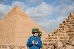 happy boy in sunglasses standing in front of the pyramides - Egypt  little traveller