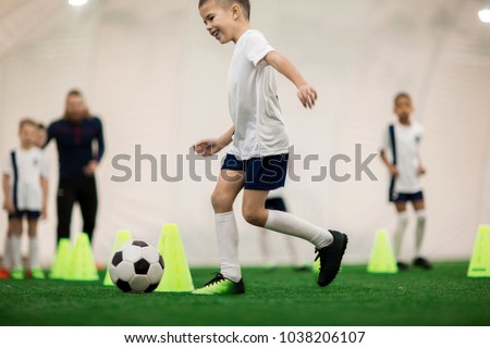 Happy boy in uniform kicking the ball while running around cones during training #1038206107