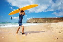Happy boy in wetsuit walk with surfboard over head in hands return from sea to the beach