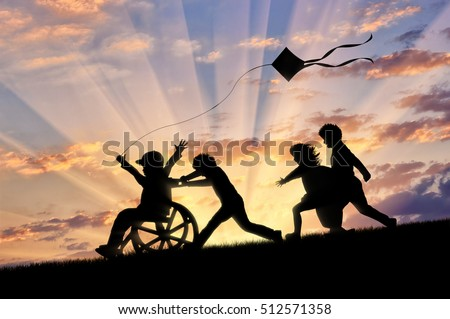 Happy boy in wheelchair playing with children and kite sunset. Concept happy child disabled