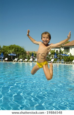 happy boy jumping into the pool , smiling, summer, resort, vacation, swimming