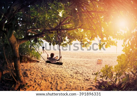 Happy boy kid on swing enjoy freedom and summer on sea shore on sunset