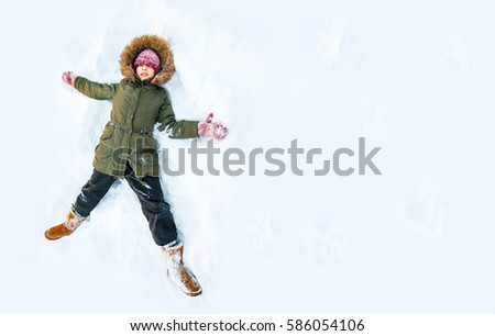 Happy boy laying on snow and making snow-angel. Boy have fun and play with snow outdoors in winter nature. Family Christmas holiday background. Walk in park with kids. Children in winter day.