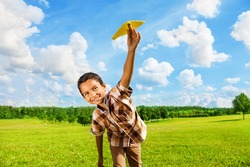 Happy boy leaning and throwing yellow paper airplane on bright sunny day in the field