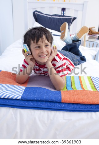 Happy boy listening to music in bedroom with headphones on