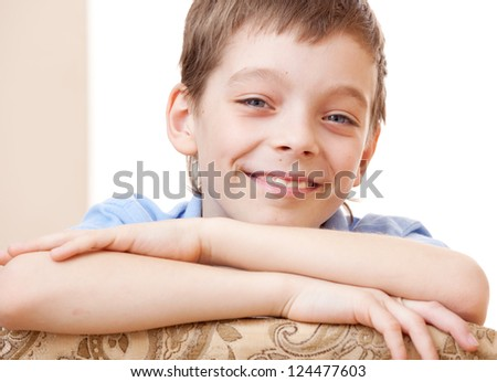 Happy boy looking at camera. Portrait smiling child at home
