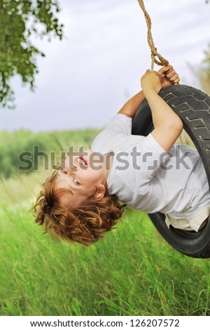 happy boy on swing outdoors