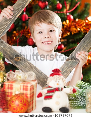 Happy boy playing against Christmas lights background