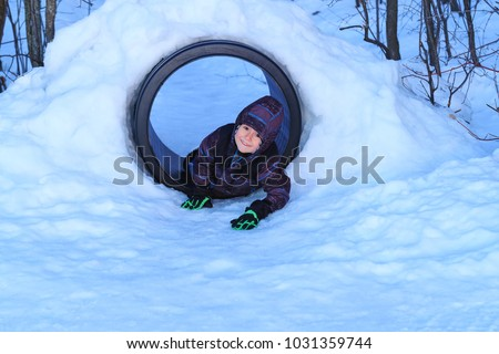 Happy boy playing in a snow tunnel. Real little boy has fun in the snow installations of public park. Awesome children play outdoors in snow. Cute boy enjoys playing in the snow playground.