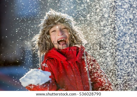 Happy boy playing in snow, winter games