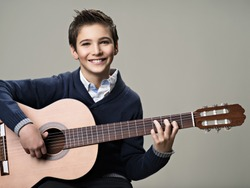 Happy boy playing on acoustic guitar. Teenager boy with classic wooden guitar