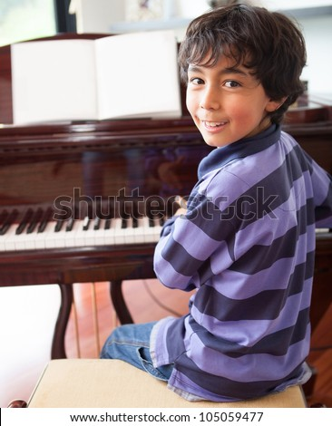 Happy boy playing the piano at home